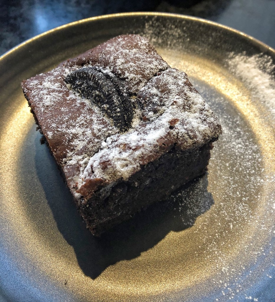 Chocolate brownie with oreo on top and dusted with icing sugar