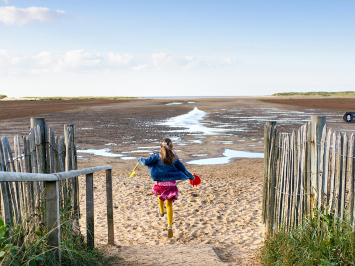 Girl running onto Holkham Beach in Norfolk